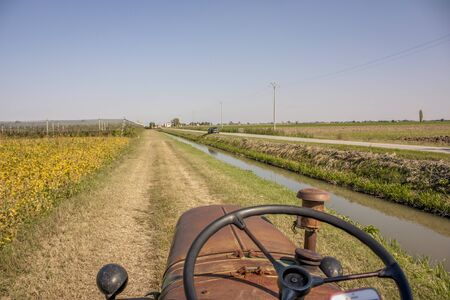 First-person image in driving a vintage tractor to cultivate farm fields and campaign.