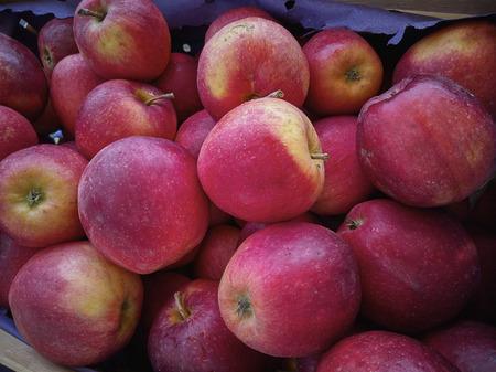 Vele rode appels te zien bij een marktkraam.
