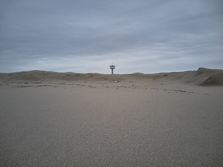 Beach with sand dunes and the aqueduct tower in the background. Reklamní fotografie