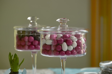 Two transparent glass containers filled with colored candies used as a decorative element.