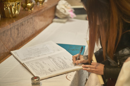 Mother signing the register of baptism during the ceremony of her sons baptism on the church altar.