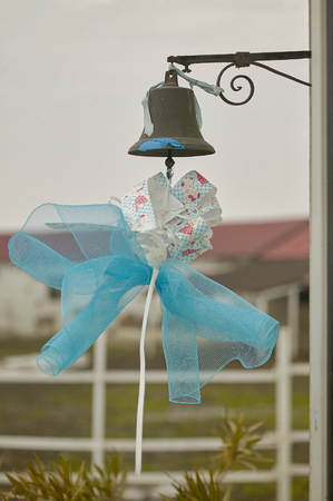 Blue bow hanging from a metal bell to symbolize the birth of a child, or to celebrate the ceremony of Catholic baptism.