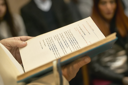 Book of the Gospel held by the priest during a Catholic celebration in church full of faithful. Stock Photo