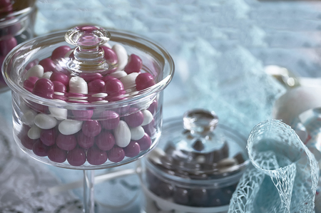 Glass container for colored candies used as a wedding favor and decoration for catholic baptism.