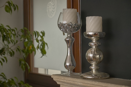 Still life with Two silver candlesticks used as a decorative element in a luxury home.