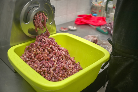 Machine to grind meat in action while filling a container of minced meat ready to use.