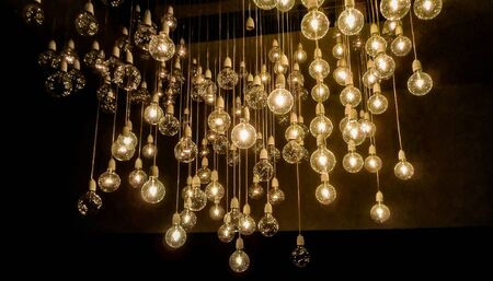 Many light bulbs hanging from wires and lit to illuminate the surrounding darkness. Фото со стока