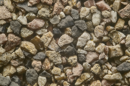 Very high definition texture of colored pebbles set in a wall.