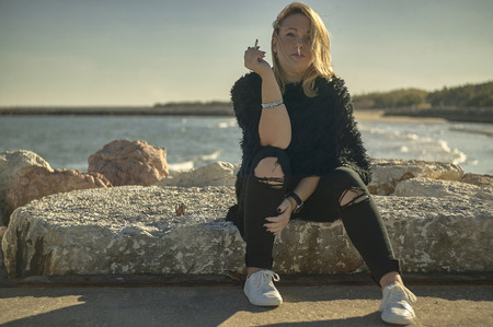 Portrait of a blonde girl sitting on the rocks at the sea with a cigarette in her hand while showing a calm and carefree expression but at the same time provocative.