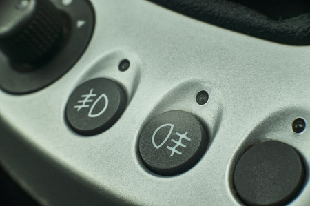 Buttons with warning lights of the fog lamps and headlights of a modern car.