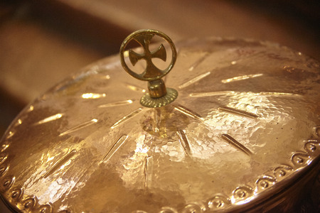 Detail of a copper bowl with a cross above used as a liturgical object in the rite of Catholic Christian baptism.