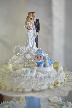 Wedding cake decorated with miniatures of the bride and groom at the top offered to diners during lunch.