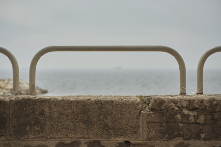 Detail of a concrete handrail with iron pipe used as a parapet on the promenade. Standard-Bild - 102833519