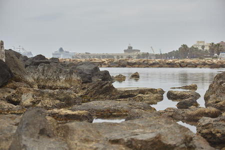 Magnificent background with rocks and drains immersed in the water with the background of the port. Фото со стока