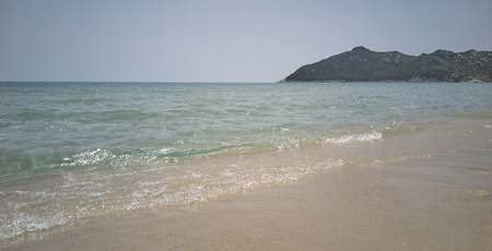 Crystalline sea with waves breaking on the sand of the beach immersed in a typical landscape of southern Sardinia. Фото со стока