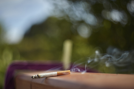 Cigarette lit on a wall with smoke coming out of the light breeze. Banco de Imagens