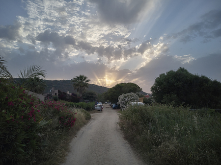 Sardinias hilly landscape of sun lit by the sunset with the sun going to disappear behind the clouds letting glimpse of its shining rays. 版權商用圖片