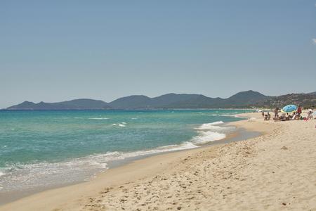 Vista sul mare blu della Sardegna con montagne e turisti che fanno il bagno sullo sfondo: lo scenario della spiaggia di costa rei durante l'estate. Archivio Fotografico