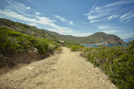 Small dirt path that runs along the coast of an area of southern Sardinia with a precipice on the side of the sea.