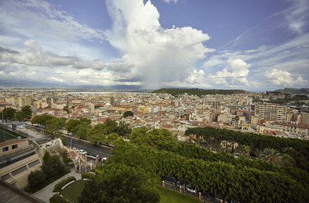 Aerial view of Cagliari city panorama under a blue sky with several white clouds.