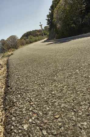 Detail of a small asphalt road flowing in the middle of Sardinia