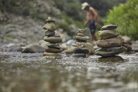 Stacks of zen rocks in a mountain sink with a disfigured man in the background that crosses the stream itself.