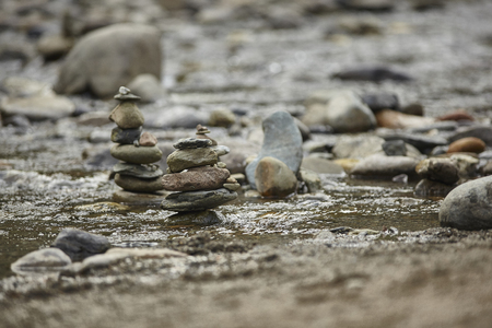 Several stacks of rocks interrupt the flow of water in the stream