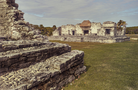 Ruins of Mayan building immersed in a green meadow: View of some parts of the Maya complex at Tulum in Mexico Stock Photo - 115803840