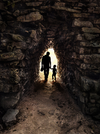 Silhouette of father and son in backlight in a small and dark stone tunnel: Image taken at Tulum in Mexico. Imagens