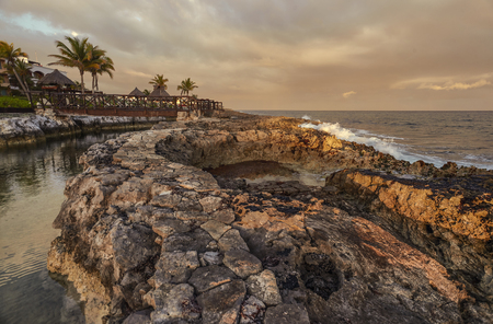 Beautiful natural swimming pool in the rocky coast at sunset in Puerto Aventuras in mexico.