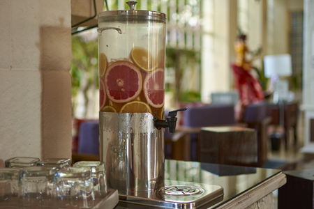 Carafe with tap full of Agua de sabor: a water with natural infusion of typical fruit of Mexico.