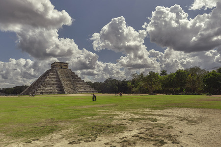 Panorama with the Pyramid of the archaeological complex of Chichen Itza in Mexico surrounded by natural vegetation under a sky with sheepish clouds and some tourists who admire it ecstatic.