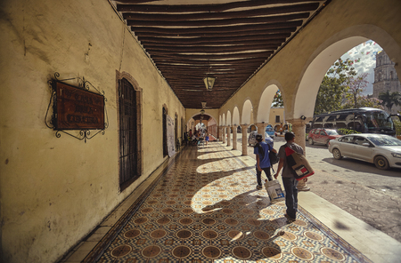 Moments of life with road traffic and people walking under the porticos of Valladolid in Mexico