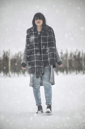 Full-length vertical shot of a dark haired girl posing under the snow Stock Photo