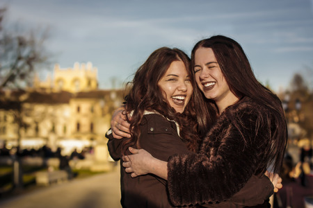 Couple of girlfriends lovingly hugging each other in an open air park: symbol of love Stockfoto - 119268061