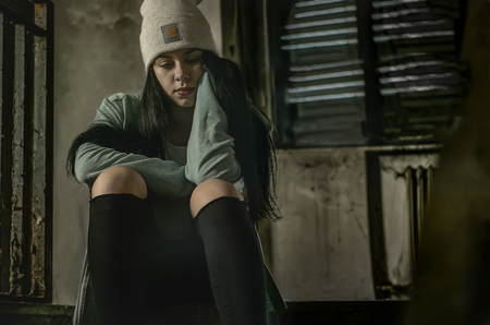 Young dark-haired girl is sitting in an abandoned building sitting on a staircase with a sad and frowned expression thinking 写真素材