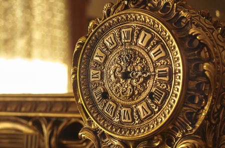 Detail of a beautiful vintage clock in the baroque style in brass.