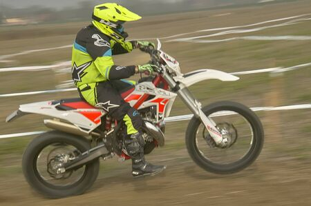 Motocross rider intent on driving his motorbike to the finish line in a motocross race on a track