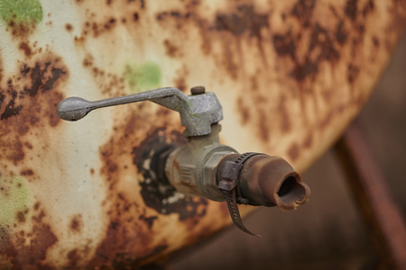 Detail of an old rusty faucet corroded by weather and weather