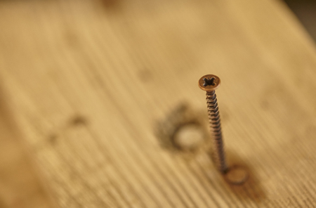 Self-tapping metal screw partially screwed into a wooden artifact inside a joinery Stock Photo