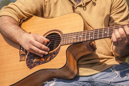 Detail of a rock musician playing a classical guitar Stock Photo