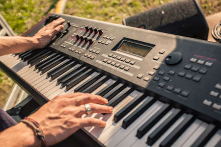 Hands of a musician play the keyboard in a masterly way at a live concert