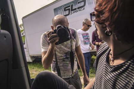 Backstage photographer in action while photographing people in a van