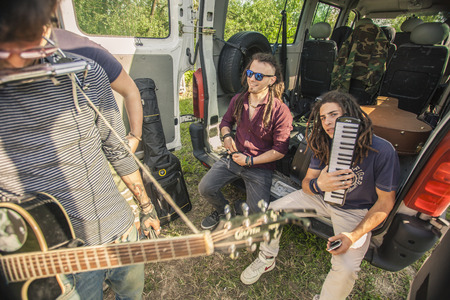 Street musicians socialize among themselves in the back of a van