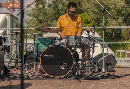 Drummer in front while playing his instrument at an outdoor concert