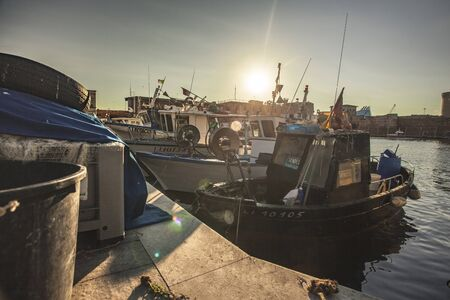 Detail of some boats moored in the port of Livorno during sunset