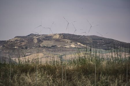 Wind turbines on the hill in the sicilian coast Banco de Imagens