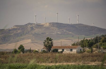 Wind turbines placed on top of a hill in Sicily, Italy, for the production of electric energy... Imagens - 124985533
