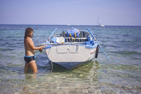 Boy moors boat on Porticello beach Stock fotó