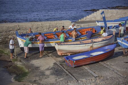 Men bring boat out of the water. Banco de Imagens